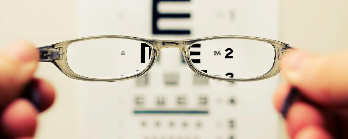 Person holding glasses in front of eyesight test